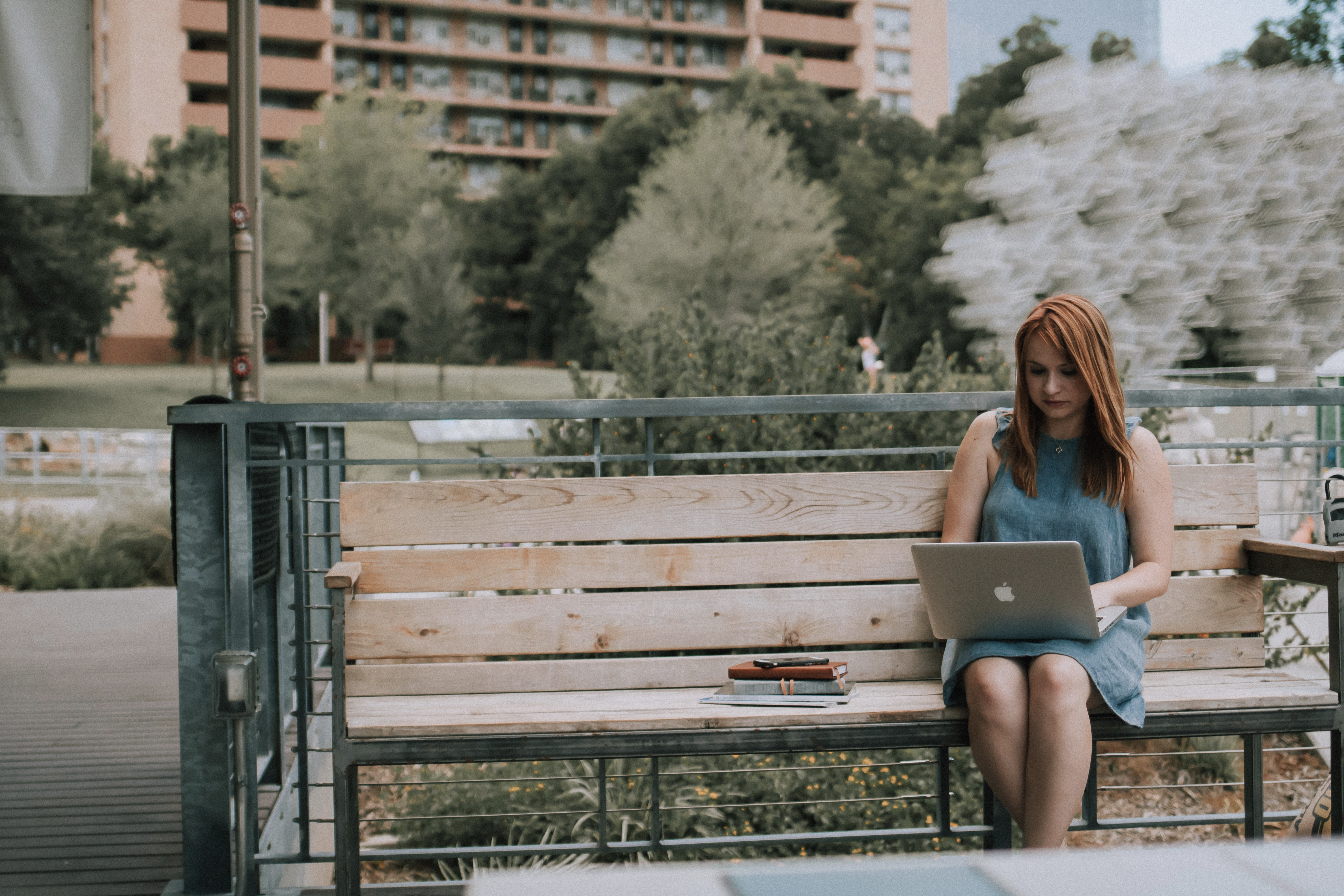 Digital nomad works from her laptop on a bench