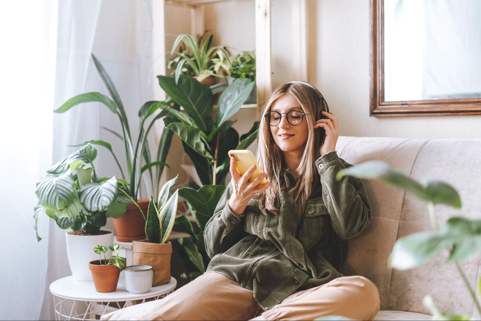 Woman looks at her phone in her furnished apartment