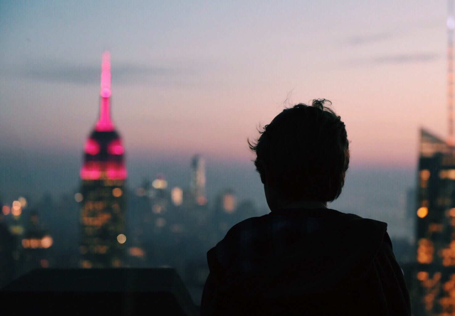 A person looks out at the New York City Skyline