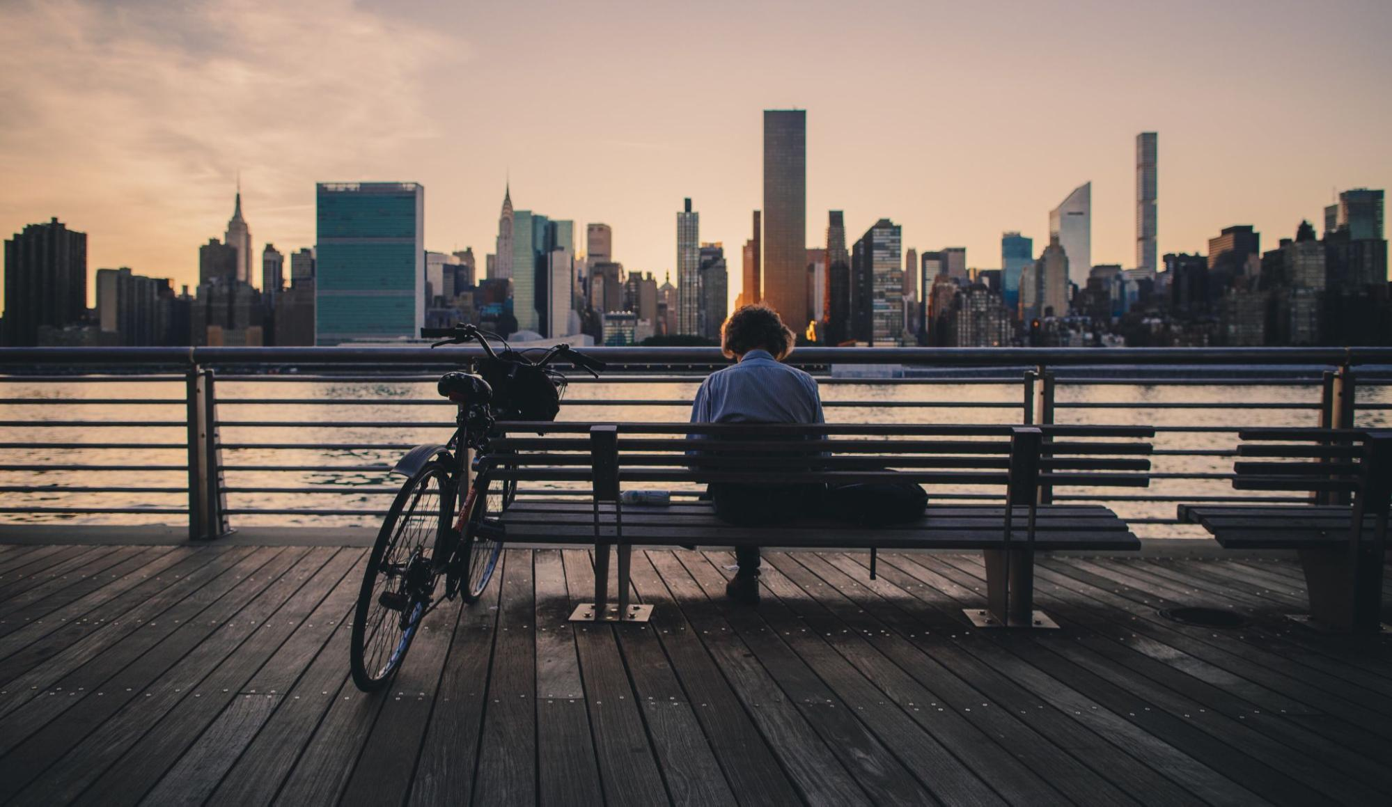 A person sits on a bench overlooking the New York City skyline.