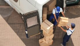 """Two men unloading boxes labeled """"dishes"""" and """"books"""" from a van in Charlotte, North Carolina."""