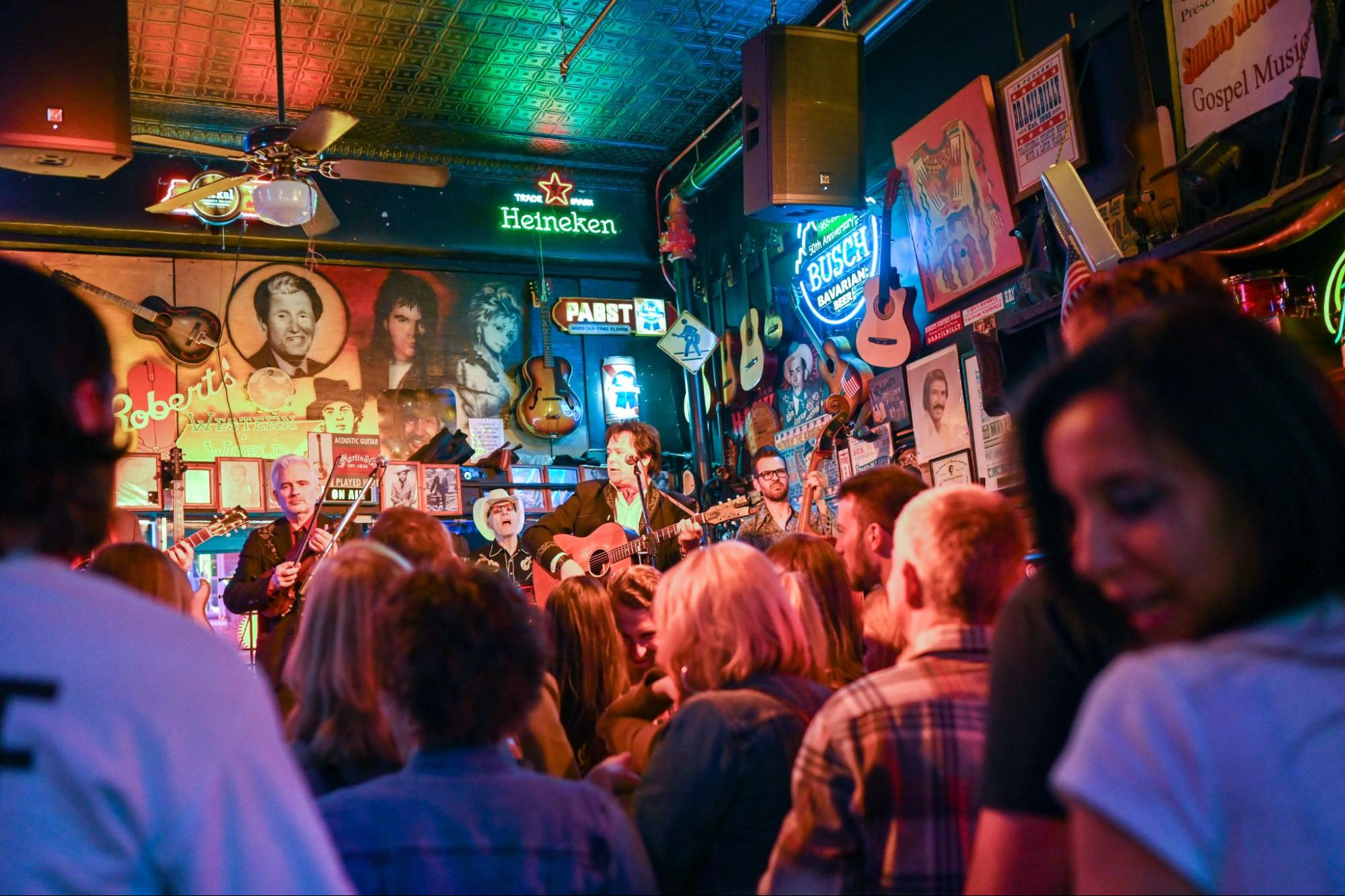 A group of people listening to a band at a country bar in Nashville, Tennessee.