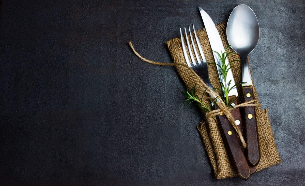 Rustic vintage set of cutlery knife, spoon, fork. Black background.