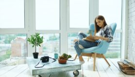Young woman reading book and drinking coffee sitting on balcony in modern loft apartment.