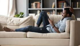 Full-length relaxed young man in glasses lying on comfortable couch, enjoying spending weekend leisure time chatting in social network on phone with friends