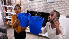 Couple uses bucket to collect leaking water from ceiling and calls a plumber to request maintenance on cell phone.