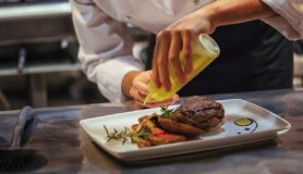 Chef in restaurant in Jacksonville rearranges and decorates food.