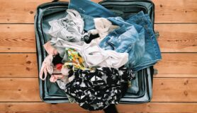 Packing suitcase with clothes before moving into a landing